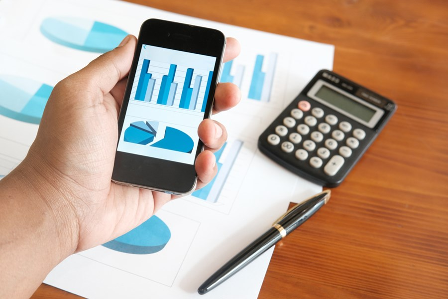 Uma mão segurando um celular que mostra gráficos; há também no plano de fundo uma calculadora e um relatório.