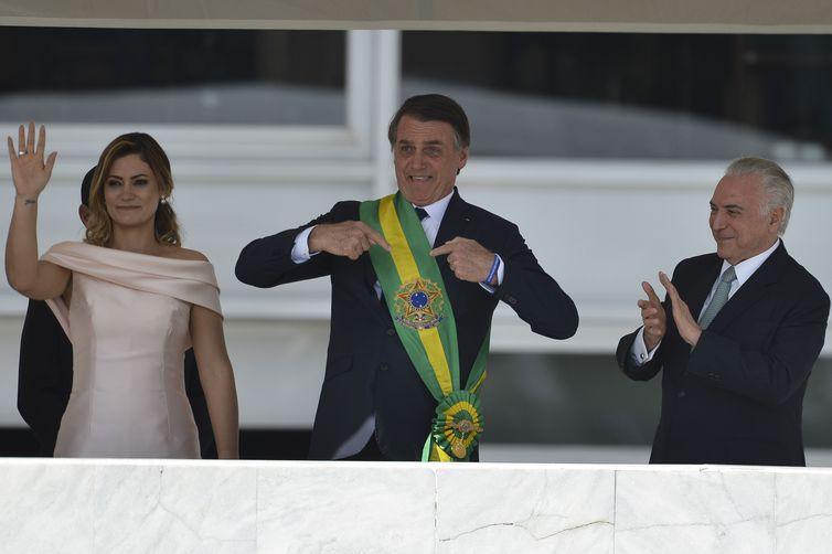 Jair Bolsonaro com a faixa presidencial ao lado de Michelle Bolsonaro e Michel Temer