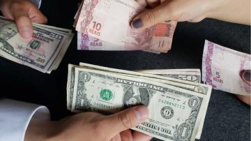 Notas de real e dólar sendo trocadas