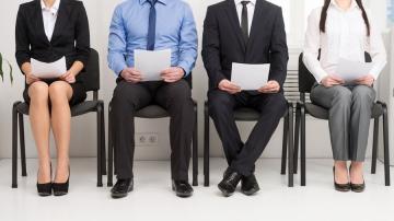 Candidatos para vaga de emprego com currículos nas mãos