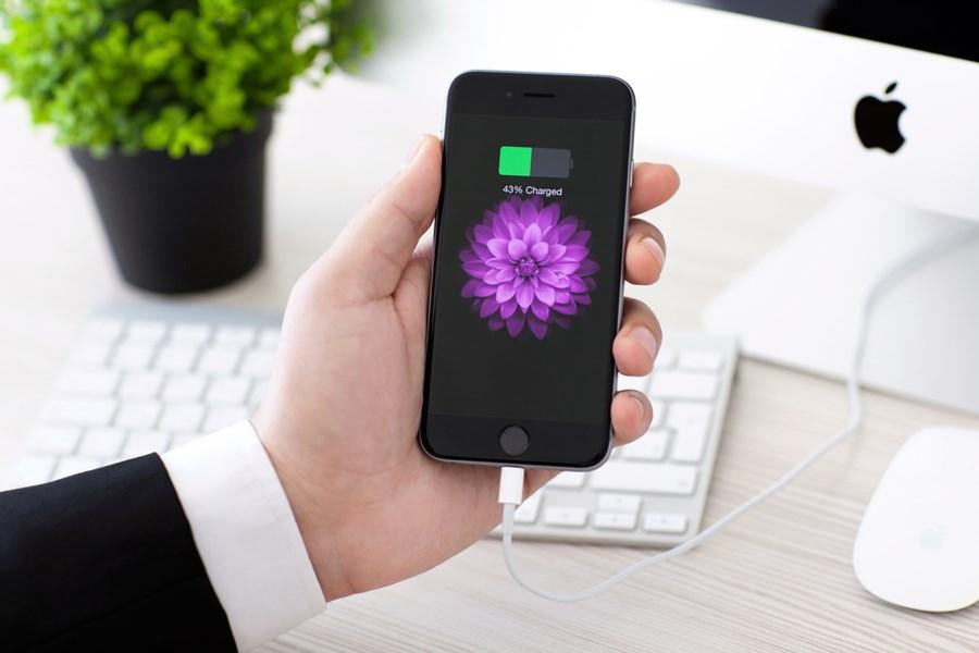 Mão segura iPhone com indicador de bateria