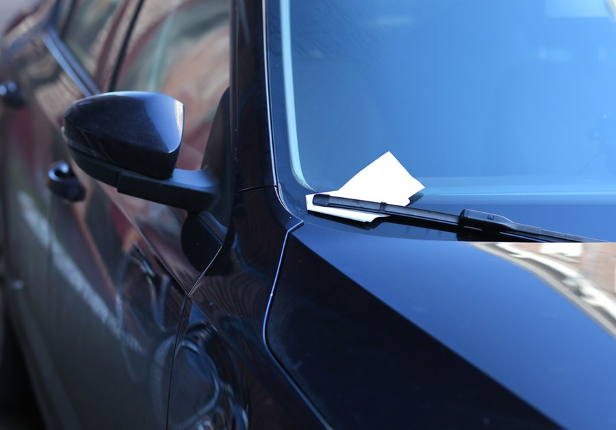 Carro com uma multa no para-brisa