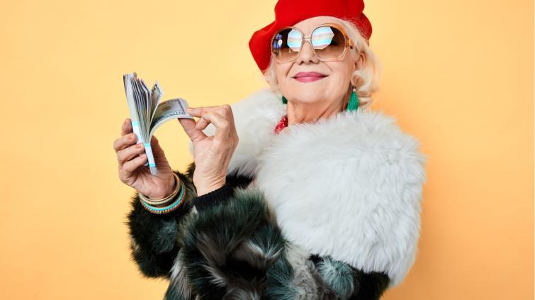 Idosa com roupas jovens e notas de dinheiro na mão
