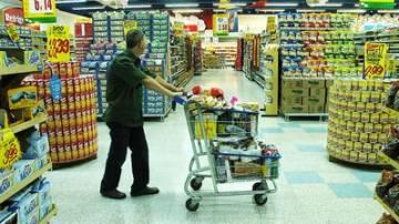 Homem com carrinho de supermercado entre as prateleiras de alimentos