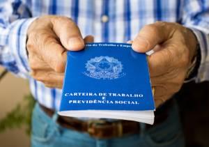 Homem idoso segurando carteira de trabalho
