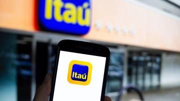Aplicativo do Itaú em primeiro plano; no segundo plano uma agência do banco