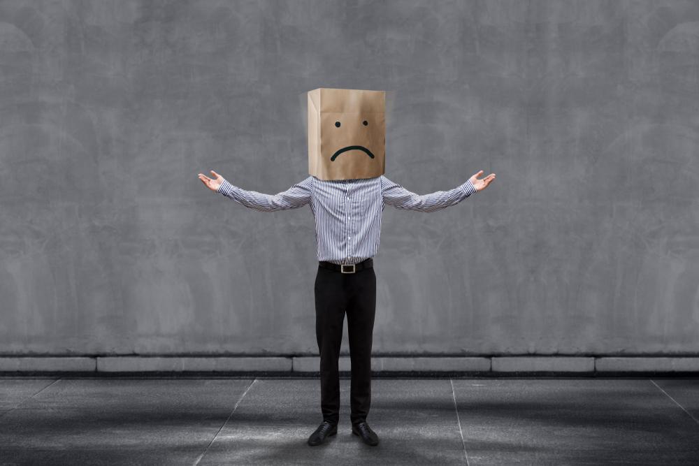 Homem com saco de papelão na cabeça, que contém um emoji triste.