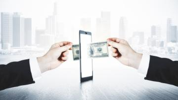 Dinheiro sendo transferido por meio de um celular para simbolizar a transação digital