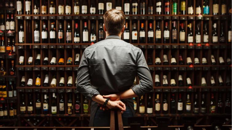 Sommelier em frente a uma estante com garrafas de vinho