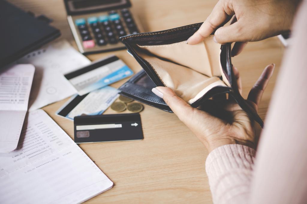 Mulher com a carteira vazia e vários cartões de crédito pela mesa