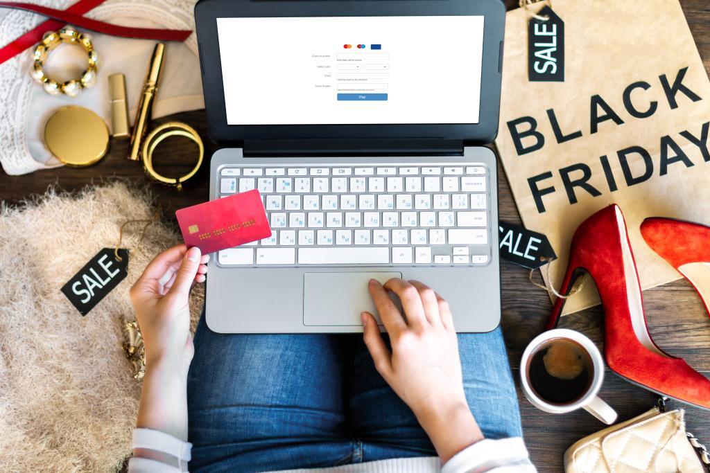 """Mulher realizando compras na internet, com uma sacola ao fundo dizendo """"Black Friday"""""""