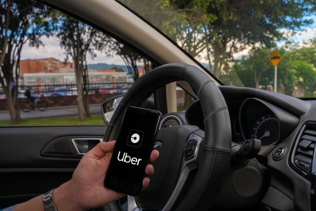 Homem segurando celular com o aplicativo do Uber