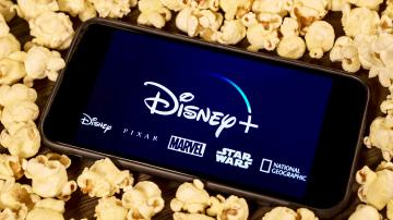 Celular com o aplicativo do Disney+ envolto de pipocas