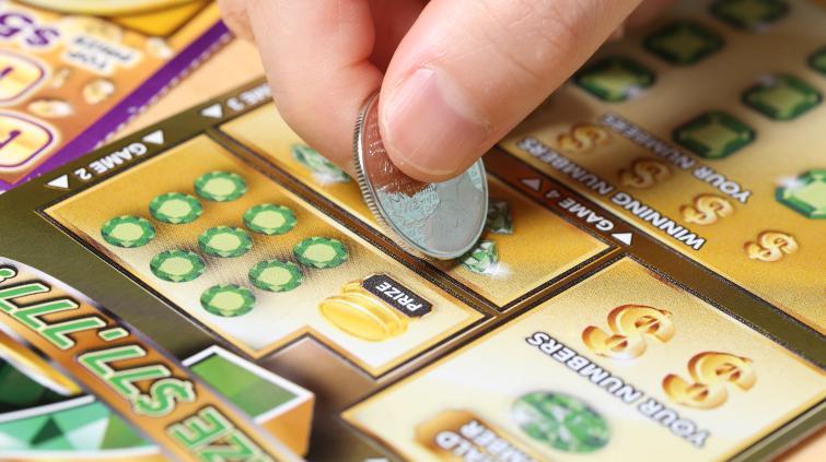 Consumidor raspando uma cartela de raspadinha da loteria