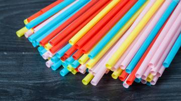 Canudos de plástico de varias cores diferentes sobre uma mesa preta