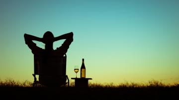 Homem relaxando tomando vinho no por do sol