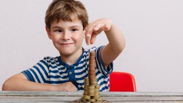 Criança fazendo uma pilha de moedas