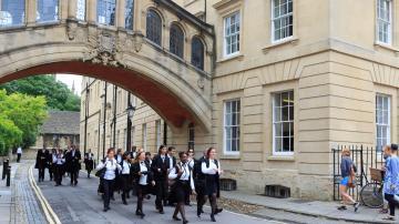 Estudantes da Universidade de Ofxord andando com seus trajes acadêmicos pretos