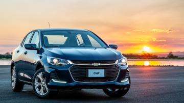 Modelo azul escuro do Onix Plus Premier 2020 em frente ao pôr do sol