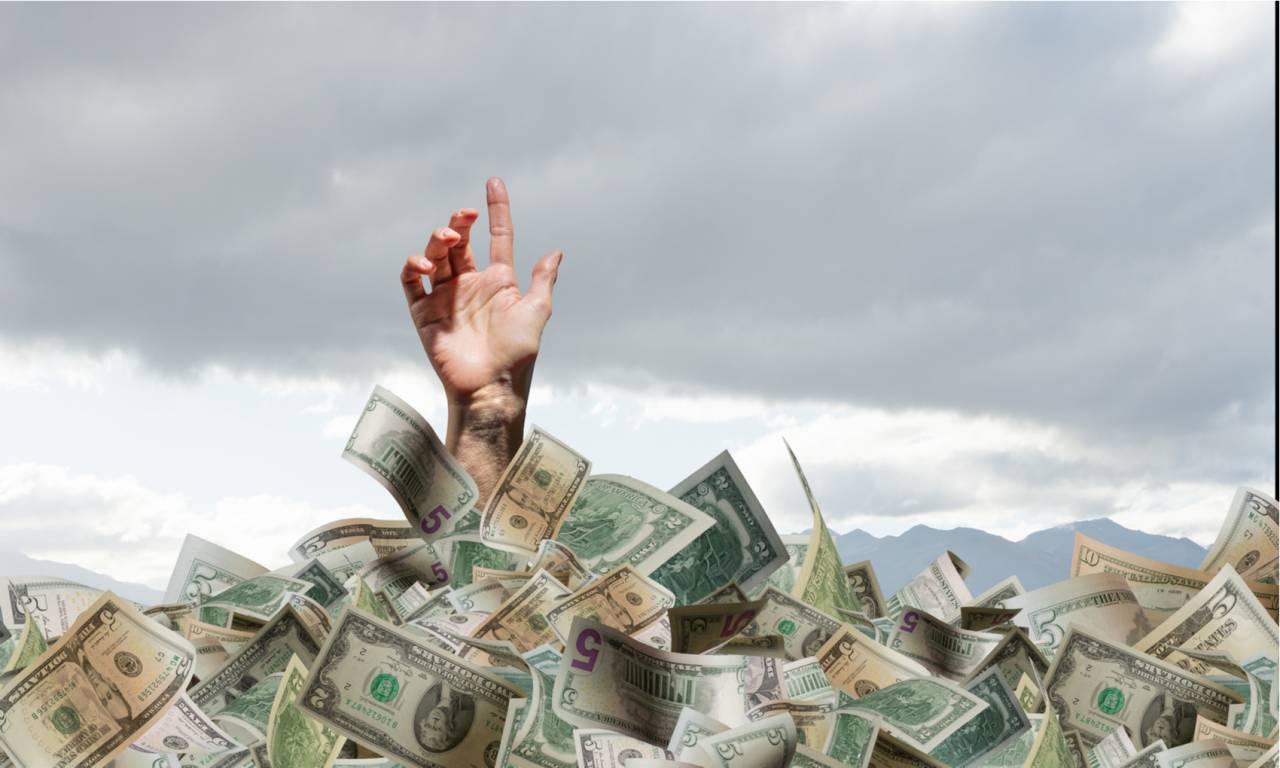 Uma pessoa se afogando em dólares