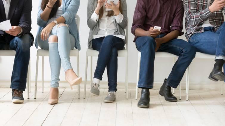 Cinco pessoas sentadas à espera da entrevista de emprego
