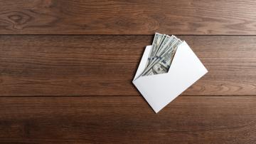 Envelope com notas de dólar sobre uma mesa de madeira