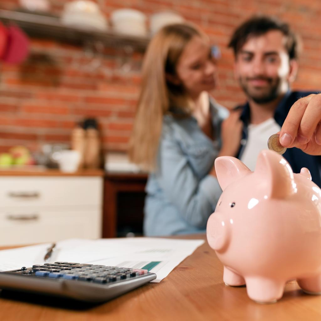 Imagem de casal feliz; homem coloca uma moeda num cofre