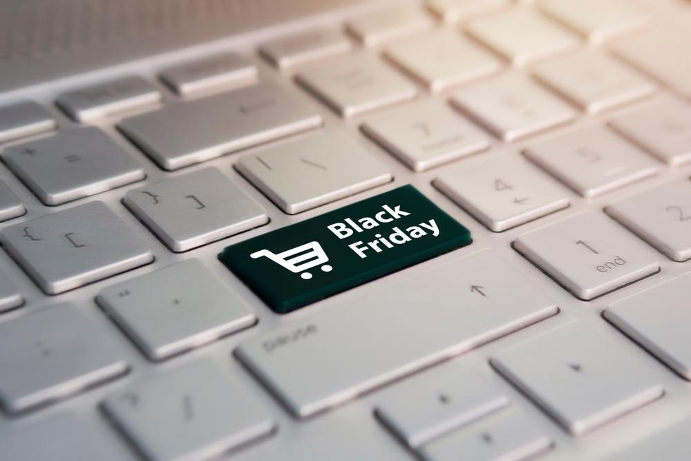 """Teclado branco de computador onde a tecla """"enter"""" foi substituída por uma tecla preta com um carrinho de compras escrito """"black friday"""""""