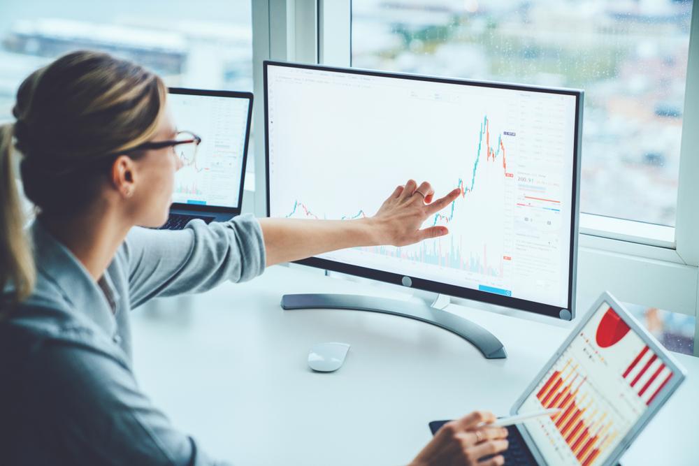 Mulher de costas analisando um gráfico no computador. Ela aponta para o gráfico com a mão esquerda