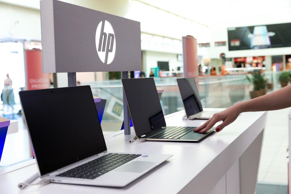 Bancada com diversos notebooks da HP, com o logo da companhia atrás