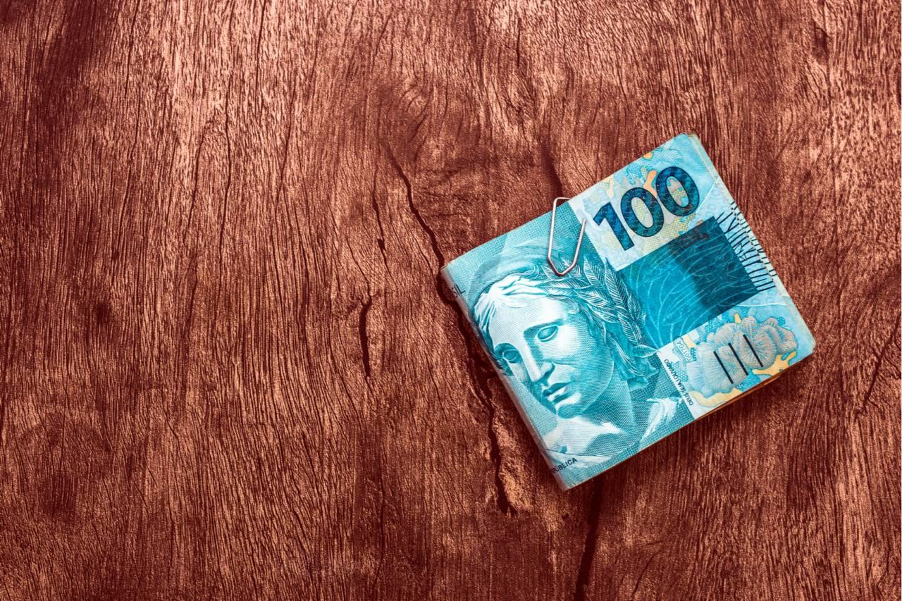 notas de R$ 100 em uma mesa de madeira reais dinheiro