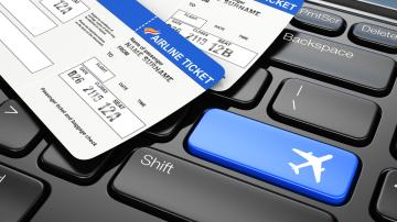 """Passagens aéreas sob um teclado de computador. A tecla """"enter"""" foi substituída por um avião"""