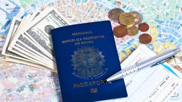 Passaporte brasileiro sob um mapa, rodeado de notas de dólares e moedas