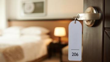 Maçaneta de quarto de hotel com uma plaquinha branca que trás o número 206