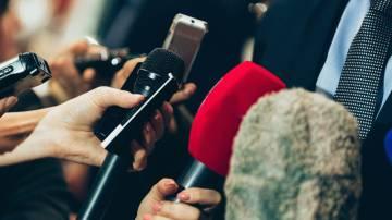 Vários jornalistas entrevistando homem de terno. Na imagem é possível ver diversos microfones apontados para o homem.