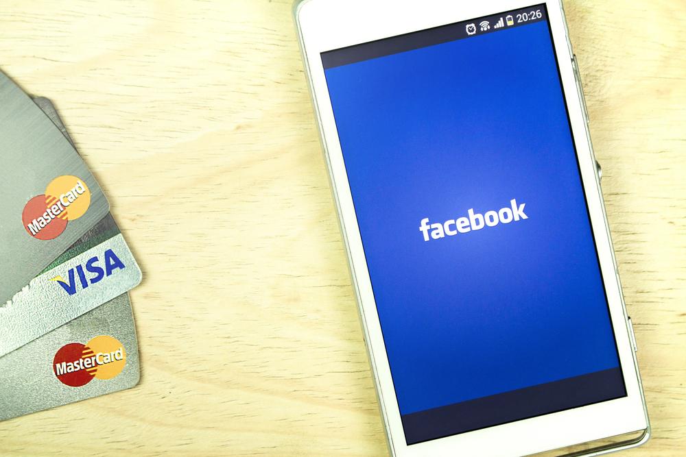 Celular com o logo do Facebook rodeado de cartões de crédito