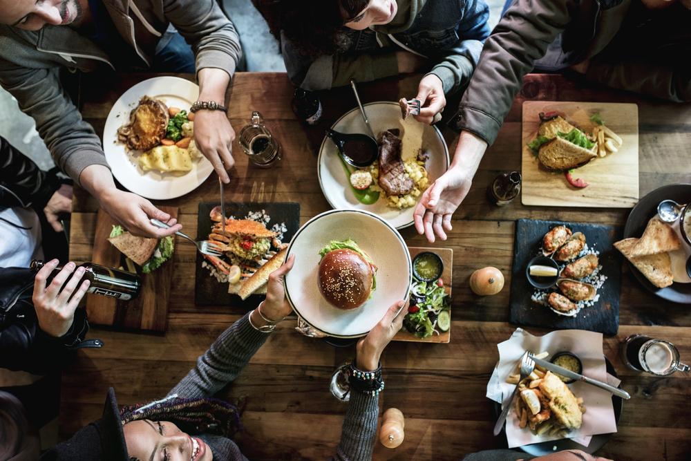 Mesa de restaurante com diversos pratos e pessoas sentadas. Uma mulher passa um prato com um hambúrguer para o outro lado da mesa