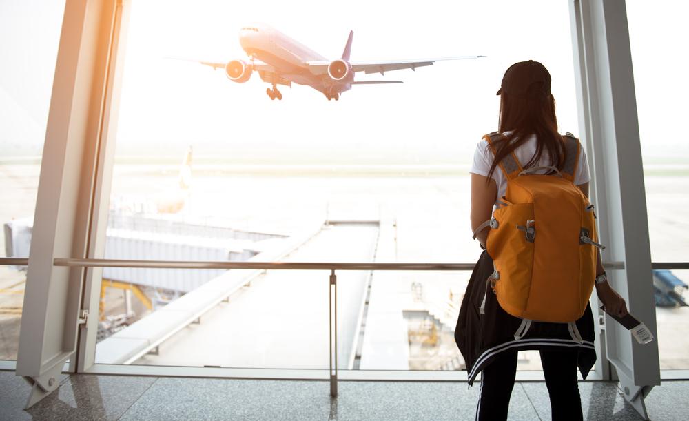 Mulher de costas olhando um avião decolar