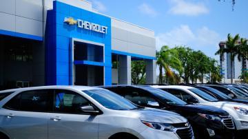 Concessionária da Chevrolet com a fachada azul e vários carros estacionados na frente da loja