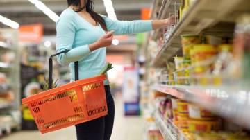 Mulher segurando cesta de supermercado enquanto escolhe alguns itens da prateleira