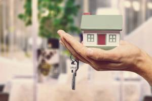 Uma mão segurando uma casa para simbolizar a compra de um imóvel