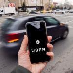 Mão segurando um celular com o logo da Uber centralizado na foto. Um carro passa no fundo da imagem