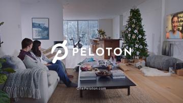 Comercial da Peloton mostra um casal sentado no sofá assitindo televisão. O logo da Peloton aparece centralizado na tela