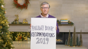 "Bill Gates segurando um cartaz escrito ""Holiday Book Recommendations 2019"""