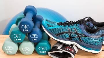 Pesos de academia com tênis de corrida apoiado