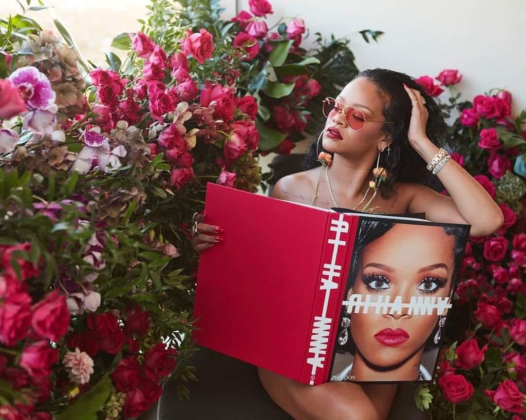 Cantora Rhianna posa sentada com um livro vermelho sob seu colo ao lado de muitas rosas