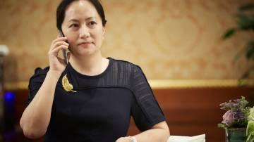Meng Wanzhou, CFO da Huawei falando ao telefone em uma mesa de jantar. Ela usa um vestido preto e fala ao celular com a mão direita