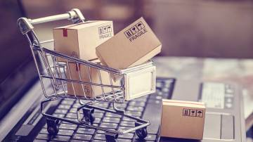 Carrinho de compras em cima de um teclado de notebook com caixas de papelão dentro dele