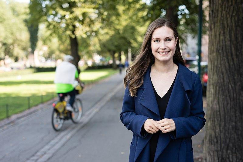 Sanna Marin parada ao lado de uma árvore com blusa azul