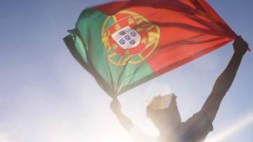 Homem segura bandeira de Portugal contra a luz